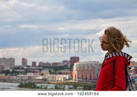 Teenager girl standing with view of the city and cloudy sky