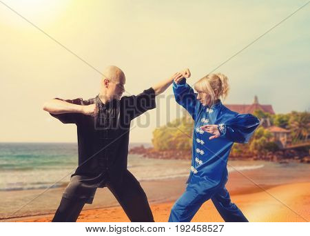 Male and female wushu fighters training on coast