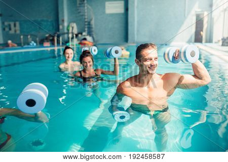 Women aqua aerobics traninig with dumbbells