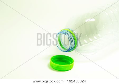 Plastic bottle and white background and water in plastic lids isolated on white.