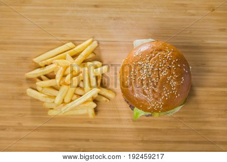 Burger with potatoes on cutting Board, top view