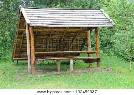 Old style wooden canopy with bench in forest park