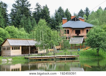 Modern cottage and a gazebo on shore of lake in Ukrainian Carpathians
