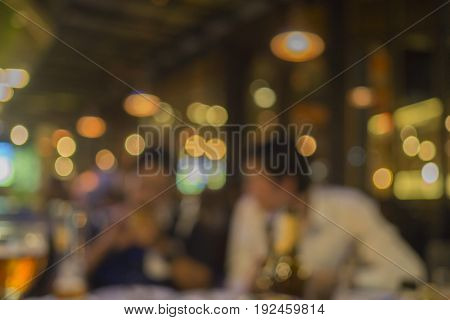 Blurred bokeh background with warm colorful lights of two man drinking in night club.