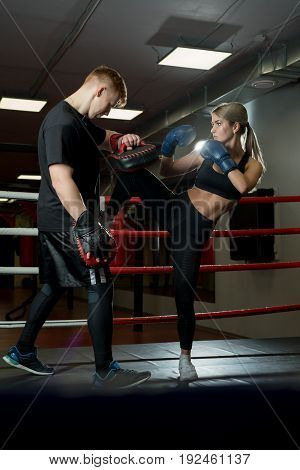 Sexy girl in boxing gloves and her boyfriend fighting in a boxing ring