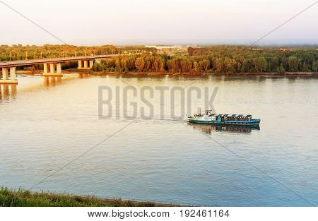 Scenic evening view of the river. The ship floats on the river under the bridge.