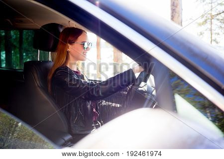 Confident and beautiful girl driving a car