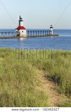The North Pier Inner and Outer Lighthouses at St. Joseph Michigan are viewed from a trial in the dunes overlooking Lake Michigan.