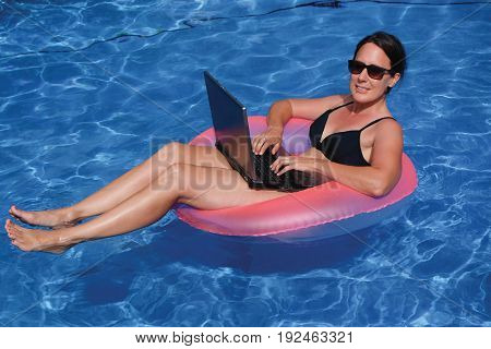 Female executive workaholic working on laptop computer in pink inflatable life ring in swimming pool on vacation