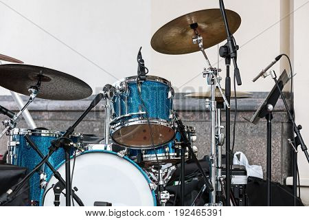 Blue Drum Set And Plates Standing On Outdoor Stage Against Wall Background