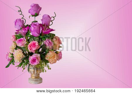 Bouquet of dark red rose flowers buds with green leaves in glass vase isolated on color background