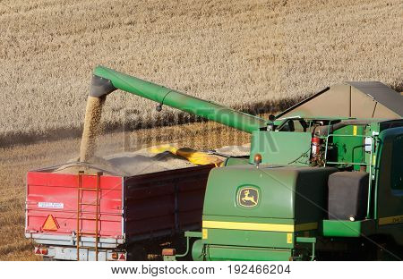 Botkyrka Sweden - August 24 2016: A green John Deere harvester drains the container for the torn seed to a tractor trailer.