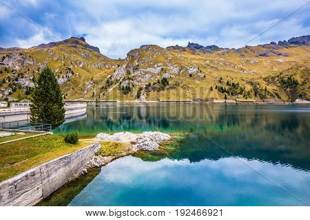 Mountain Lake Lago di Fedaia, Dolomites. Powerful dam blocked the lake. The concept of ecological and extreme tourism. Glacial lake with clear cold water