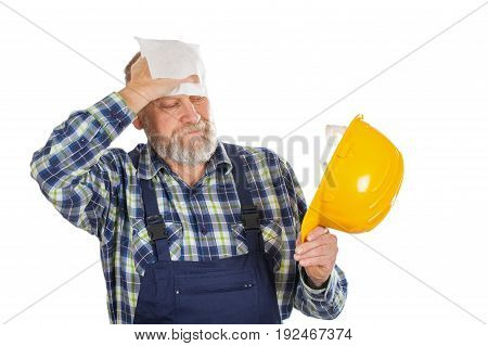 Picture of an elderly builder with construction instruments in his hands posing on isolated background