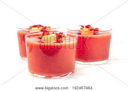 A side view of a salmorejo, traditional Spanish cold soup, served in glasses, garnished with jamon and croutons, on a white background with a place for text