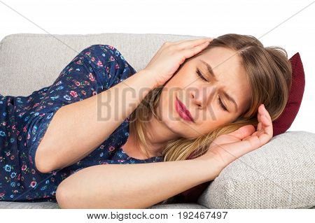 Picture of an attractive young woman lying on the couch at home having a headache
