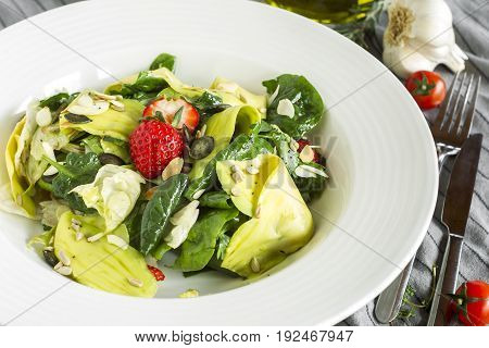 Salad with spinach avocado iceberg lettuce and strawberry.