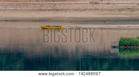 Yellow row boat with blue oars next to a sandbar in a river with a grassy island in the right foreground.