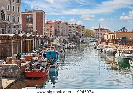 LIVORNO, ITALY - APRIL 14 2015 - picturesque view of the characteristic old port canal with fishing boats in the Italian town Leghorn on April 14, 2015 in the city Livorno, Tuscany, Italy