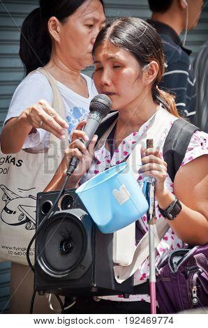 BANGKOK THAILAND-JUNE 19: Unidentified blind woman singing for donate money at the market on June 19 2011 in BangkokThailand.