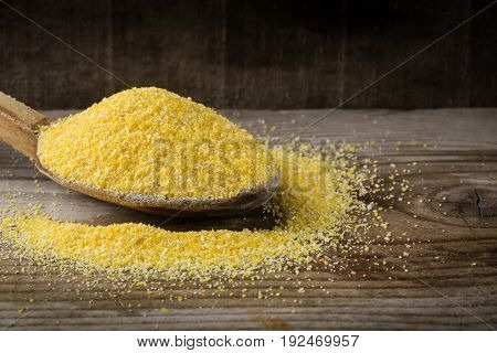 Organic cornflour in wooden spoon on wooden rustic background.