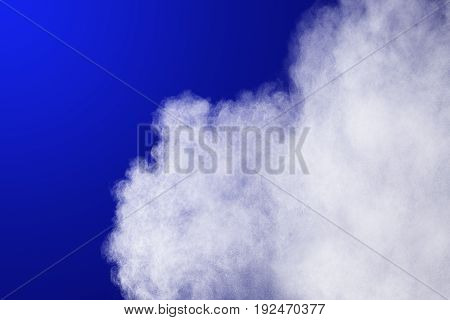 Abstract White powder explosion on blue background.