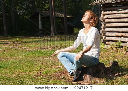 A young and beautiful woman meditating in nature.