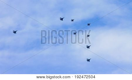 Formation of an aerobatic team aircrafts that consist of eight fighter jets flyby in an airshow.