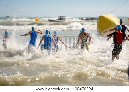 Starting for the swimming test of the athletes of triathlon blurred