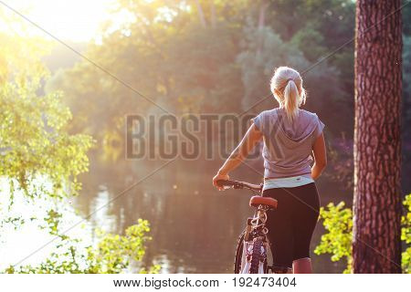 Beautiful blonde girl riding on a Bicycle on a bright Sunny summer day. Rear view.