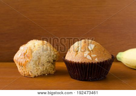 Two pieces of delicious banana cup cake topped with sliced almond in dark brown paper cup over orange brown teakwood table with wooden background. Fresh baked cup cakes with space selective focus.