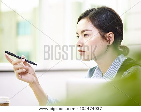 young asian business woman working in office holding a pen thinking.