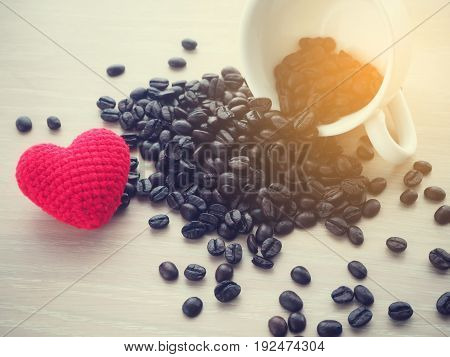 close up of fresh coffee bean and red heart shape sign warm tone.