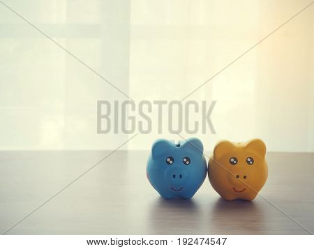 wood table with two piggy bank on white drape texture background warm tone.