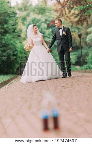 The happy walk of the newlyweds in the park at the blurred background of the bottles