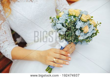 wedding bouquet in hands of bride. the bride sits on a bench and holding a bouquet