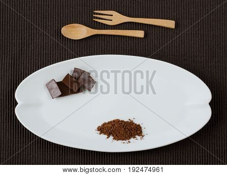 Flat lay image of rectangle dark chocolate pieces and 100% cocoa powder on ceramic white plate shaped as banana leave over dark brown cotton place mat with wooden spoon and fork