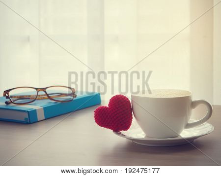 wood office table with red heart shape sign on cup of latte coffee and modern eyeglasses on blurry white curtain texture background view from front wood table.