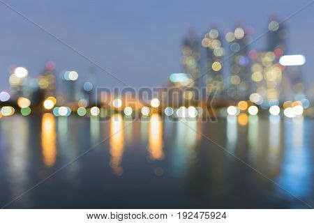 Night blurred bokeh light office building with water reflection abstract background