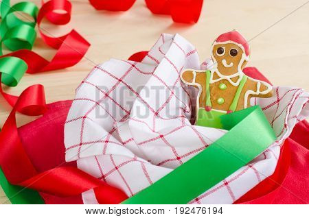 Happy gingerbread man decorated with red green and white colour icing on red and white napkins for christmas party or new year's eve on wooden table with red and green ribbons for holiday celebration