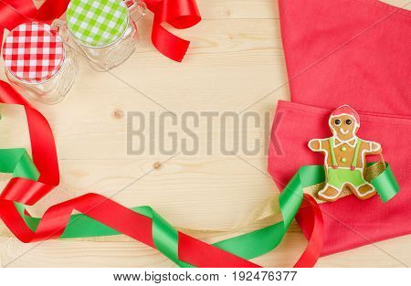 Flat lay of happy gingerbread man decorated with red green & white colour icing on red napkin for christmas party on wooden table with red and green ribbons for holiday celebration and copy space