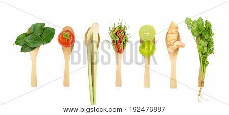 Flat lay of fresh Thai delicious spicy & sour Tom Yum dish's ingredients of lemon grass cilantro galangal kaffir lime leaves limes spicy bird peppers & tomato isolated on white space background