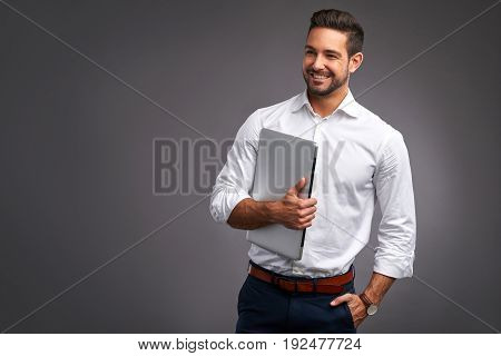 A confident handsome young man holding a laptop in a white shirt