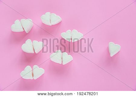 Marshmallows in heart shapes for Valentines day over pink paper background to show sweet love candy for couples