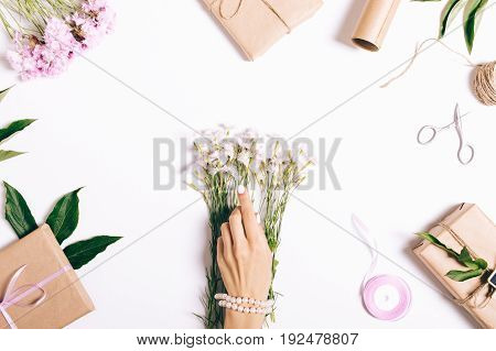 Female Hands With A Manicure Make Decorations For The Holiday On A White Table