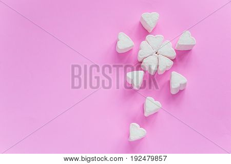 Marshmallows in heart shapes for Valentines day over pink paper background grouped like sakura flower bouquet to celebrate sweet love candy for couples