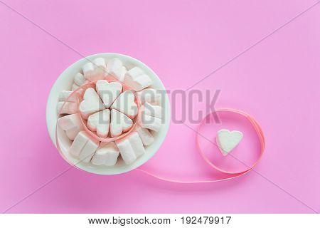 Marshmallows in heart shapes for Valentines day over pink paper background and ribbon to celebrate sweet love candy for couples selective focus