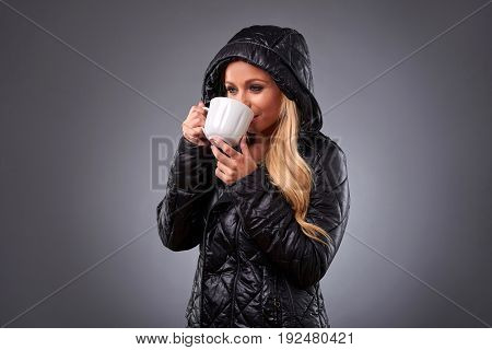 A beautiful young woman standing in a winter jacket and drinking from a mug