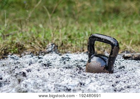 Kettle bell. Old rusty Kettle Bell in the ashes