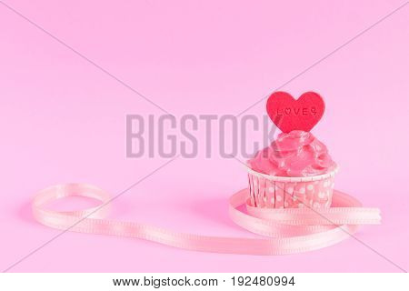 Sweet homemade cupcake with red heart shaped fondant over pink background with ribbon and copy space for text decoration